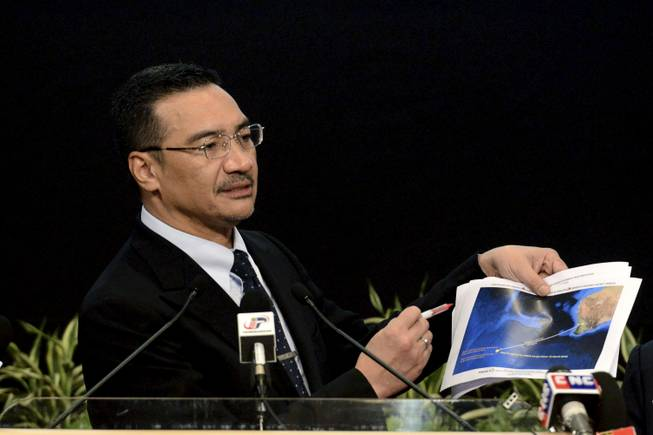 Malaysia's Defense Minister and acting Transport Minister Hishammuddin Hussein shows a printout of the latest satellite image of objects that might be from the missing Malaysia Airlines plane, at Putra World Trade Center in Kuala Lumpur, Malaysia, Wednesday, March 26, 2014. Hishammuddin said the objects were seen close to where three other satellites previously detected objects.