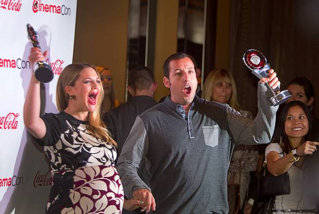 Drew Barrymore and Adam Sandler hold up awards as they arrive for the Big Screen Achievement Awards during CinemaCon, the official convention of the National Association of Theatre Owners, at Caesars Palace Thursday, March 27, 2014. Barrymore was the recipient of the Female Star of the Year award. Sandler received the Male Star of the Year award.