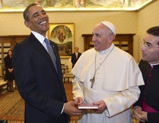 Pope Francis and President Barack Obama smile as they exchange gifts, at the Vatican Thursday, March 27, 2014.