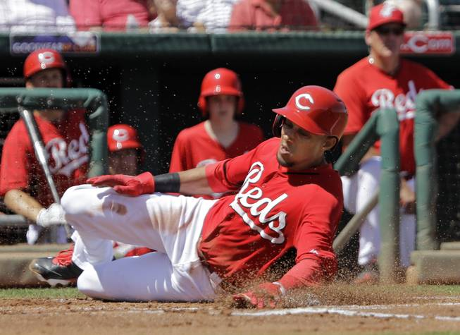 Cincinnati Reds' Billy Hamilton slides home to score from third base on a ground out by Brandon Phillips in the first inning of a spring exhibition baseball game against the Arizona Diamondbacks on Thursday, March 27, 2014, in Goodyear, Ariz.