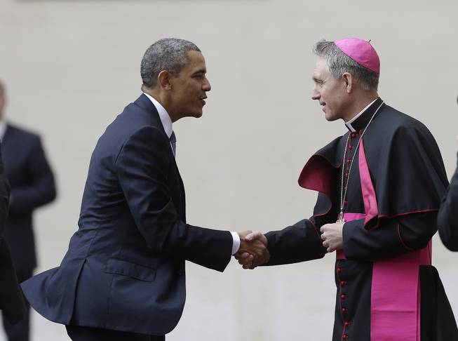 President Barack Obama, left, is welcomed by Archbishop George Gaenswein, prefect of the papal household, as he arrives at the Vatican to meet Pope Francis, Thursday, March 27, 2014.