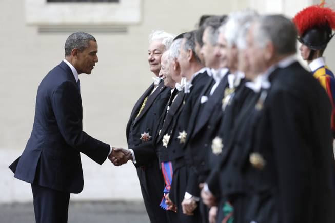 President Barack Obama is welcomed by Papal gentlemen as he arrives at the Vatican to meet Pope Francis, Thursday, March 27, 2014.
