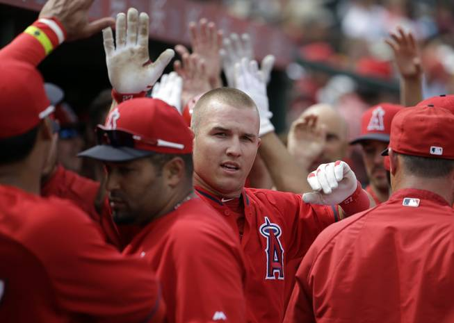 Los Angeles Angels' Mike Trout is congratulated after scoring during an exhibition spring training baseball game against the Chicago White Sox Thursday, March 13, 2014, in Tempe, Ariz.