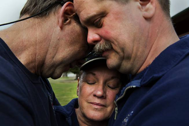 Darrington Fire District 24 volunteer firefighters, Jeff McClelland, left, Jan McClelland, center, and Eric Finzimer embrace each other Wednesday, March 26, 2014, in Darrington, Wash., after saying a prayer for the victims and survivors of the massive mudslide. They were among the first responders to the mudslide.