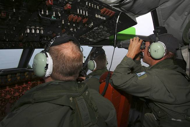In this Wednesday, March 26, 2014, photo, Flight Engineer Ron Day, right, on board a Royal Australian Air Force AP-3C Orion, searches for the missing Malaysia Airlines Flight 370 in the southern Indian Ocean.