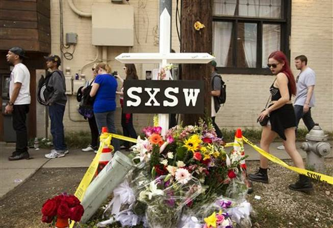 In this March 15, 2014, file photo, a cross and flowers are outside The Mohawk in Austin, Texas, as a memorial to the people who died after being struck by a drunken driving suspect during the South By Southwest festival. On Thursday, March 27, 2014, police said a fourth person, DeAndre Tatum, had died of injuries in the crash.
