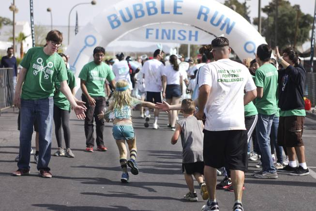 Volunteers, green t-shirts, cheer on participants as they approach the finish line during the 5k Bubble Run in downtown Las Vegas Saturday, March 29, 2014.