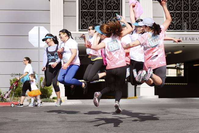 Participants jump in the air for a group photo during the 5k Bubble Run in downtown Las Vegas Saturday, March 29, 2014.
