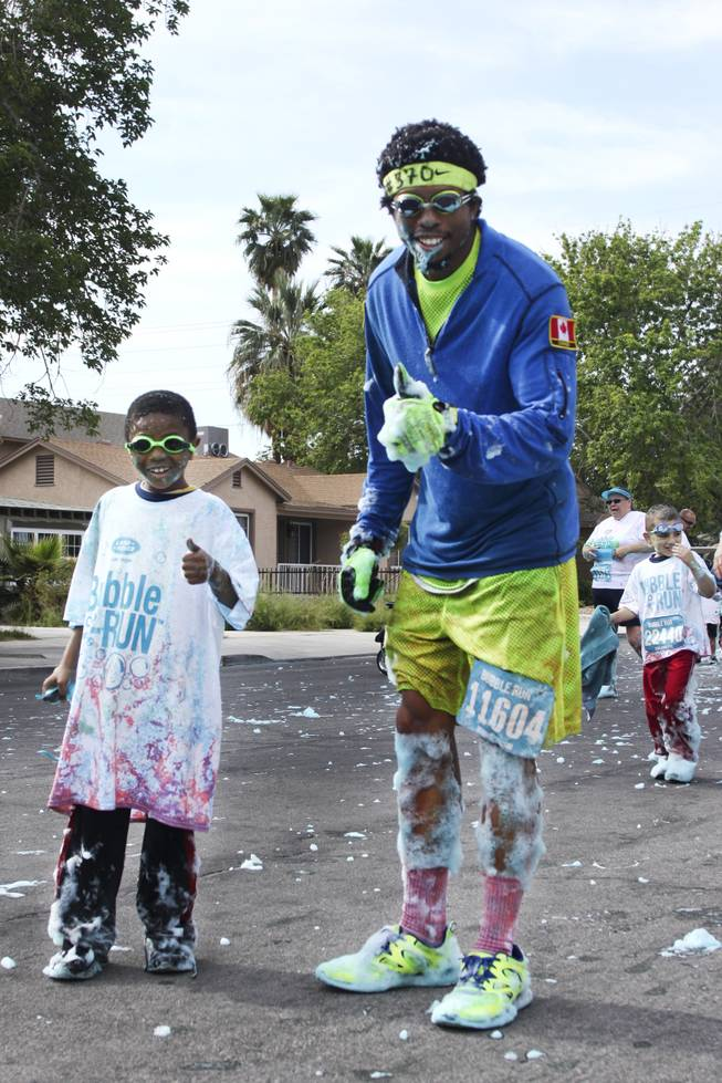 Robert Johnson, left, and his uncle, Matthew Thompson, center front, give an approving thumbs up during the 5k Bubble Run in downtown Las Vegas Saturday, March 29, 2014.