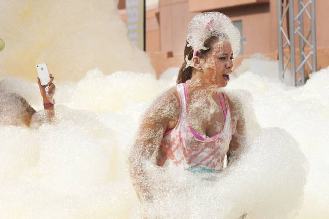 A participant comes out of the yellow foam bog station covered in foam during the 5k Bubble Run in downtown Las Vegas Saturday, March 29, 2014.