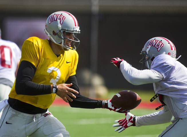 UNLV QB Nick Sherry hands off the ball to RB Adonis Smith during practice at Rebel Park on Friday, March 28, 2014.
