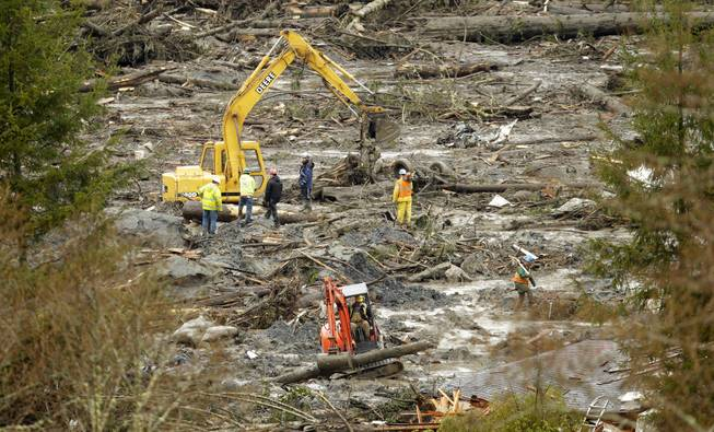 Workers use heavy equipment to clear trees and other debris, Thursday, March 27, 2014, as the search continued for victims of the massive mudslide that struck Saturday near Darrington, Wash.