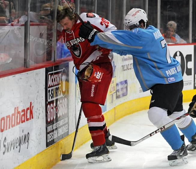 Las Vegas Wranglers forward Robbie Smith (20) takes a shot to the head near the boards from Alaska Aces defenseman James Martin (7) during the third period of play on Friday night.