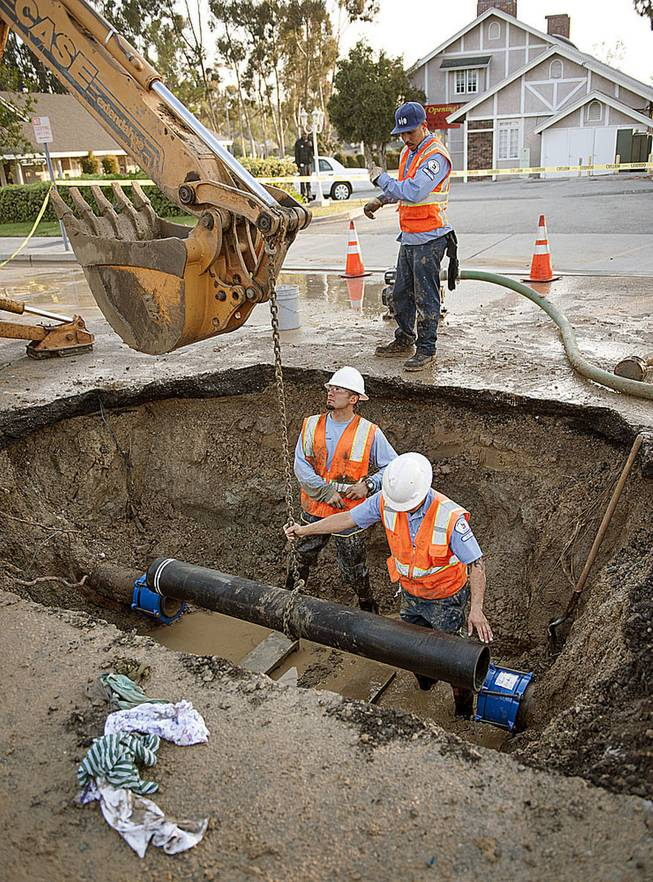 City of Fullerton maintenance workers Ernie Vejar, left, Eric Becerra and Andrew Grajeda, above, lower in a new section of pipe Saturday, March 29, 2014,   as they work on repairing a main water line in Fullerton, Calif. More than 100 aftershocks have rattled Orange County south of Los Angeles where a magnitude-5.1 earthquake struck Friday.  Despite the relatively minor damage, no injuries have been reported. (AP Photo/The Orange County Register, Ken Steinhardt)   MAGS OUT; LOS ANGELES TIMES OUT