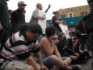 Protesters sit in downtown Albuquerque, N.M. during a rally Sunday March 30, 2014,  against a recent police shootings.