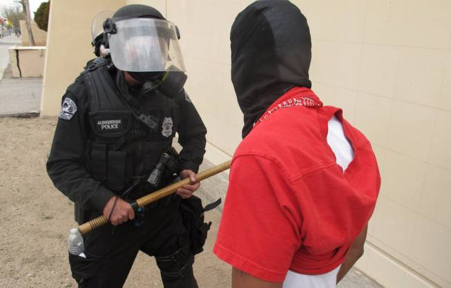 A protester faces off with an Albuquerque officer during a rally against recent police shootings in Albuquerque, N.M. on Sunday March 30, 2014.