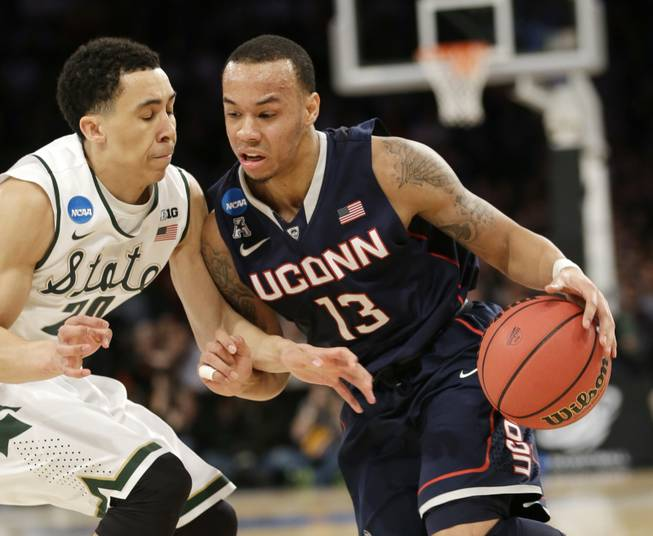 Connecticut's Shabazz Napier, right, moves the ball around Michigan State's Travis Trice in the first half of a regional final at the NCAA college basketball tournament on Sunday, March 30, 2014, in New York.