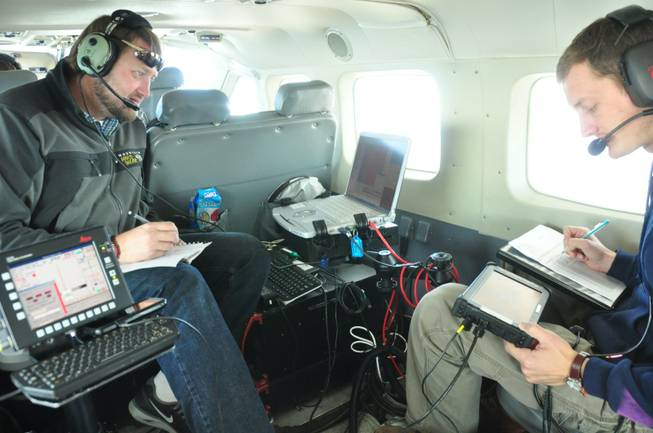 In this photo taken in October 2012, released by WSI, a Quantum Spatial Company, sensor operators Lennie Rummel left, and Drew Wendeborn, right, are shown inside a helicopter taking measurements with LIDAR, a high-tech laser system mounted on the aircraft, to build a detailed elevation map of the terrain above Omak, Wash. The maps can be used by planners and homeowners to begin to assess landslide risk.