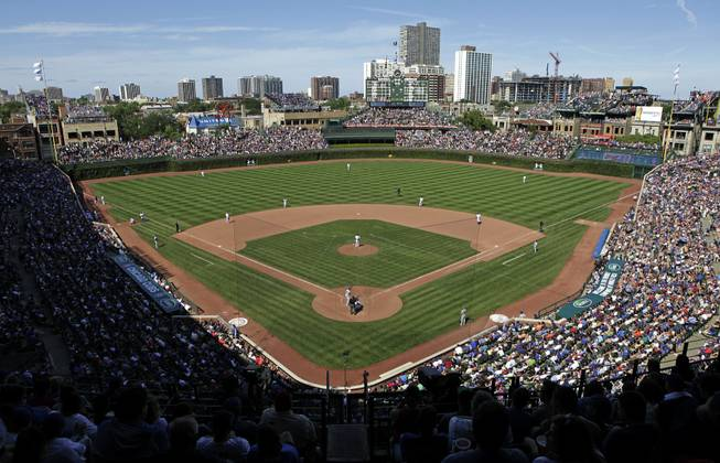 In this Aug. 4, 2013, file photo, the Los Angeles Dodgers play the Chicago Cubs at Wrigley Field in Chicago. Wrigley Field has been the site of so much heartbreak that some fans who spend their whole lives waiting for a winner ask their families, if they can pull it off, to sneak their ashes inside to be scattered in the friendly confines — a final resting place to keep on waiting. But before years turned into decades and decades turned into a century without a World Series title, Wrigley Field was in first time and time again in changing the way we watch baseball and the experience for fans in ballparks around the country. The historic ballpark will celebrate it's 100th anniversary on April 23, 2014.