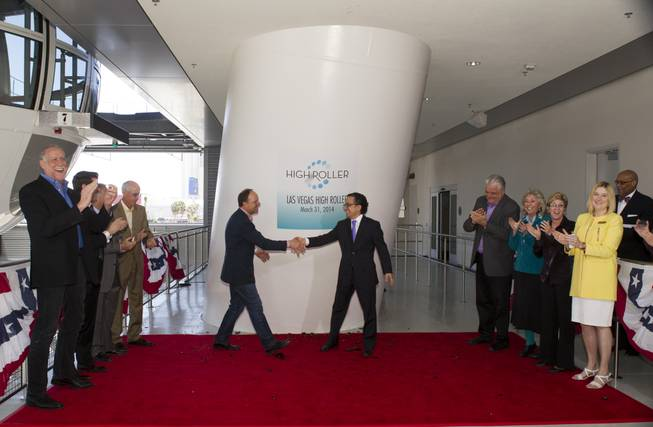 David Codiga, left, Linq executive project director, breaks a bottle of champagne shakes hands with Tariq Shaukat, Caesars Entertainment chief marketing officer, after a christening ceremony for the 550-foot-tall High Roller observation wheel Monday, March 31, 2014. The observation wheel, the tallest in the world, is part of the Linq project, a $550 million development by Caesars Entertainment Corp.