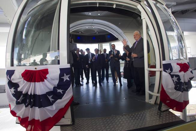 Special guests, executives and elected officials enter a cabin for the first official ride on the 550-foot-tall High Roller observation wheel Monday, March 31, 2014. Clark County Commission Chairman Steve Sisolak waves at right. The observation wheel, the tallest in the world, is part of the Linq project, a $550 million development by Caesars Entertainment Corp.