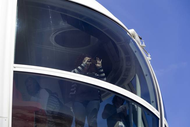 A woman takes a photo from a cabin during a ride on the 550-foot-tall High Roller observation wheel Monday, March 31, 2014. The observation wheel, the tallest in the world, is part of the Linq project, a $550 million development by Caesars Entertainment Corp.