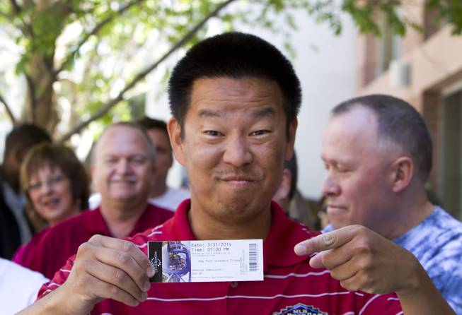 Van Kim of Phoenix shows off his ticket before the first public ride on the 550-foot-tall High Roller observation wheel Monday, March 31, 2014. Kim says his ticket was the first sold to the public. The observation wheel, the tallest in the world, is part of the Linq project, a $550 million development by Caesars Entertainment Corp.