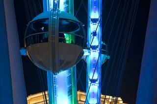People ride in cabins of the 550-foot-tall High Roller observation wheel Monday, March 31, 2014. The observation wheel, the tallest in the world, is part of the Linq project, a $550 million development by Caesars Entertainment Corp. The ride is now open to the public.