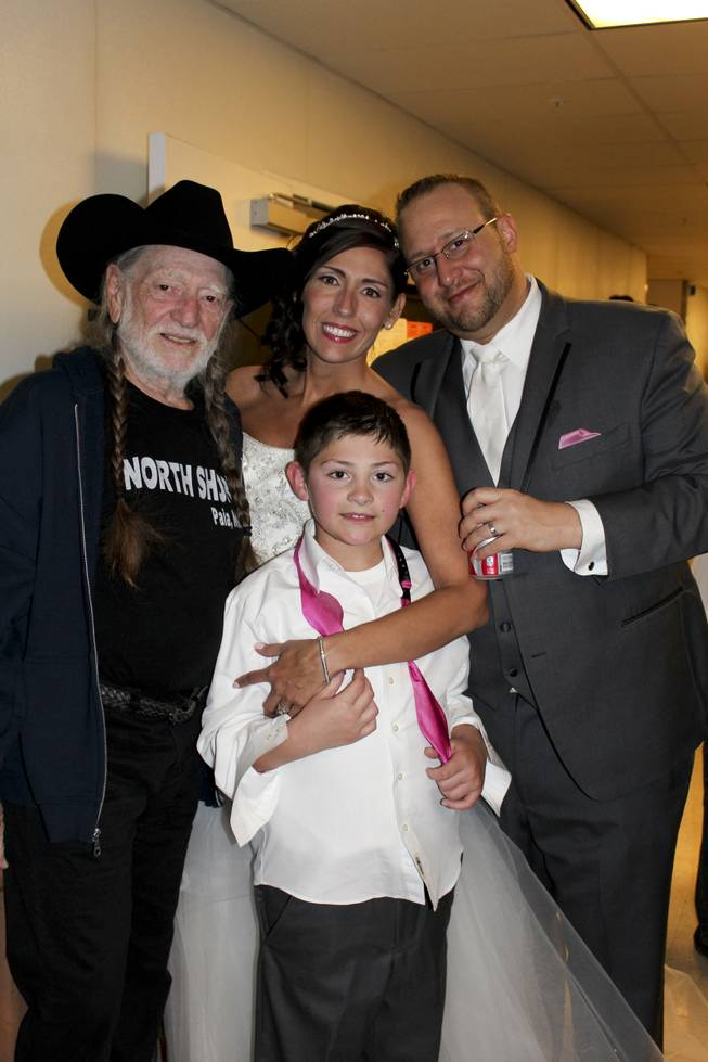 Willie Nelson poses with newlyweds who were having their wedding reception concurrent to his concert at The Westin at Lake Las Vegas Monday, March 31, 2014.