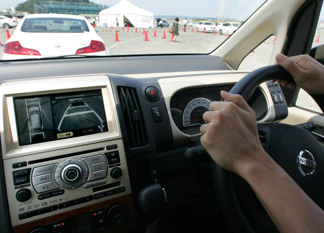 An employee of Nissan Motor Co., tries to park the automaker's Serena equipped with four cameras at the front, the rear, and two rear mirrors of the car while looking at a monitor showing the virtual bird-eye view of the vehicle's position during a press tour at Nissan's Oppama plant in Yokosuka, Kanagawa prefecture, south of Tokyo, Monday, Aug. 6, 2007.