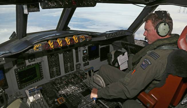 A Royal New Zealand Air Force P-3 Orion's co-pilot and Squadron Leader Brett McKenzie controls the pane while searching for the missing Malaysia Airlines Flight MH370 in the southern Indian Ocean, Monday, March 31, 2014.
