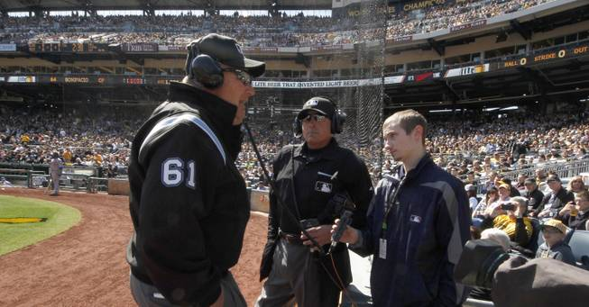 First base umpire Bob Davidson (61) and home plate umpire John Hirschbeck, center, talk over headsets as a play at first base is being reviewed in the fifth inning during the opening day baseball game between the Pittsburgh Pirates and the Chicago Cubs on Monday, March 31, 2014, in Pittsburgh. Chicago Cubs manager Rick Renteria requested a replay on an out call.