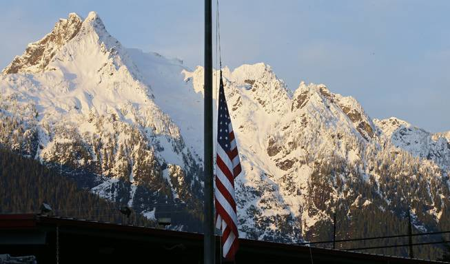 A U.S. flag hangs at half-staff with Whitehorse Mountain behind, during the early morning of Monday, March 31, 2014, at the fire station in Darrington, Wash.