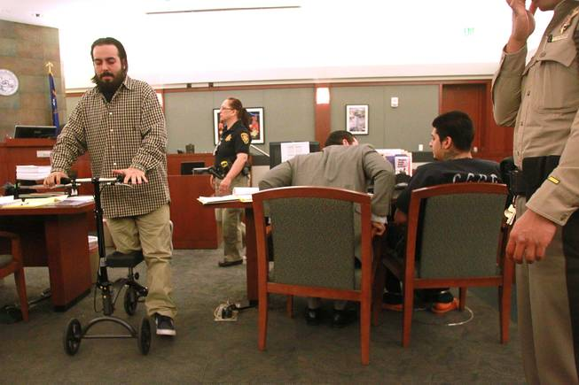 Shooting victim Christian Flores uses a rolling platform on his way out of the courtroom and past Peter Andrade Jr. during Andrade's preliminary hearing on attempted murder and other charges Tuesday, April 1, 2014.