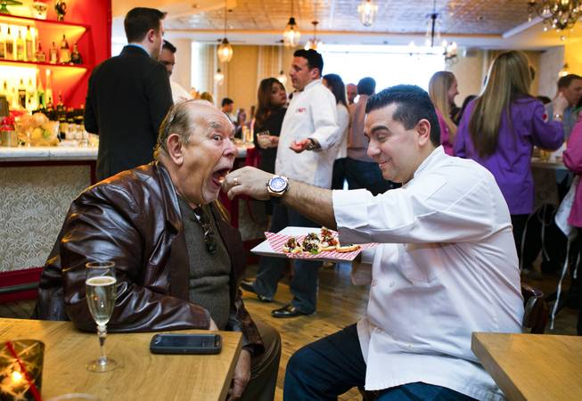Robin Leach is fed a tasty treat by chef Buddy Valastro, who is celebrating the opening of Carlo's Bakery in the Venetian with friends on Monday, March 31, 2014.