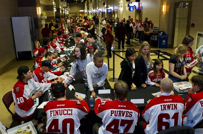 Players with the Las Vegas Wranglers Professional Hockey Club sign autographs for fans after their last home game of the regular season in the Orleans Arena on Tuesday, April 1, 2014.