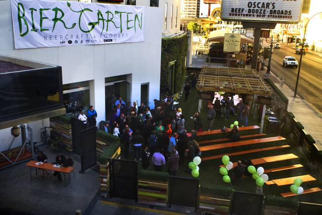 Guests gather on the natural grass of the new Bier Garten at the Plaza Hotel and Casino during grand opening celebrations on Tuesday, April 1, 2014.