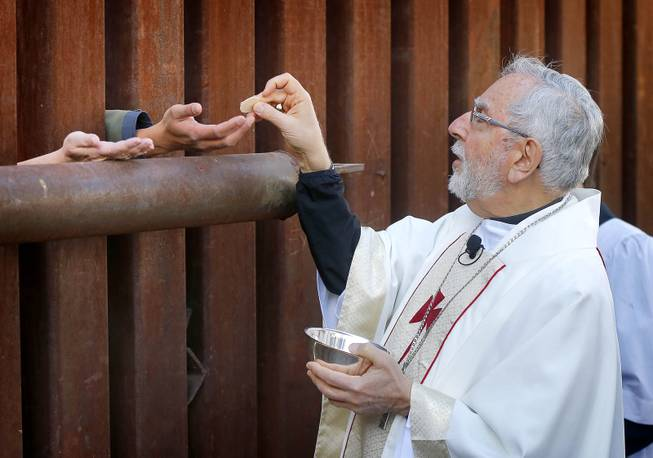 Most Reverend Gerald F. Kicanas, Bishop of Tucson, offers communion to people on the Mexican side of the international border, Tuesday, April 1, 2014, in Nogales, Ariz.