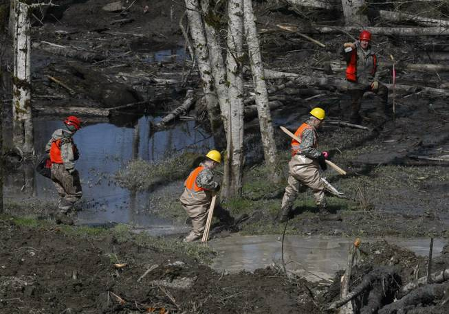 Workers trudge through the mud at the scene of the deadly March 22 mudslide, on Monday, March 31, 2014, in Oso, Wash.