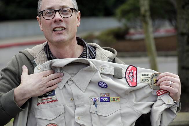 Geoff McGrath holds his Boy Scout scoutmaster uniform shirt for the Seattle troop he led, Tuesday, April 1, 2014, in Bellevue, Wash.