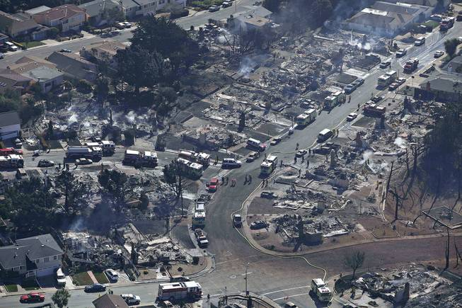 Firefighters and rescue crews work among damage caused by a pipeline explosion and an ensuing massive fire in a residential neighborhood in San Bruno, Calif., Sept.10, 2010.
