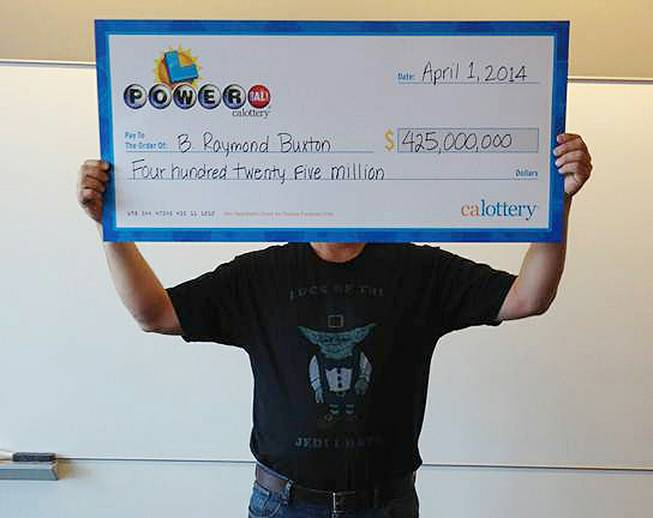 This photo provided by the California Lottery shows Powerball winner B. Raymond Buxton holding a check for $425 million, Tuesday, April 1, 2014, in Sacramento.