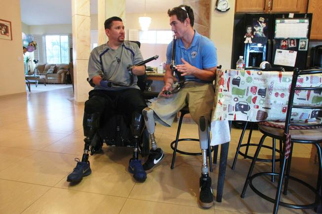 Amputee Eddie Garcia talks with Rudy Garcia-Tolson from the Challenged Athletes Foundation about the new prosthetics he will be receiving Wednesday, April 2, 2014.
