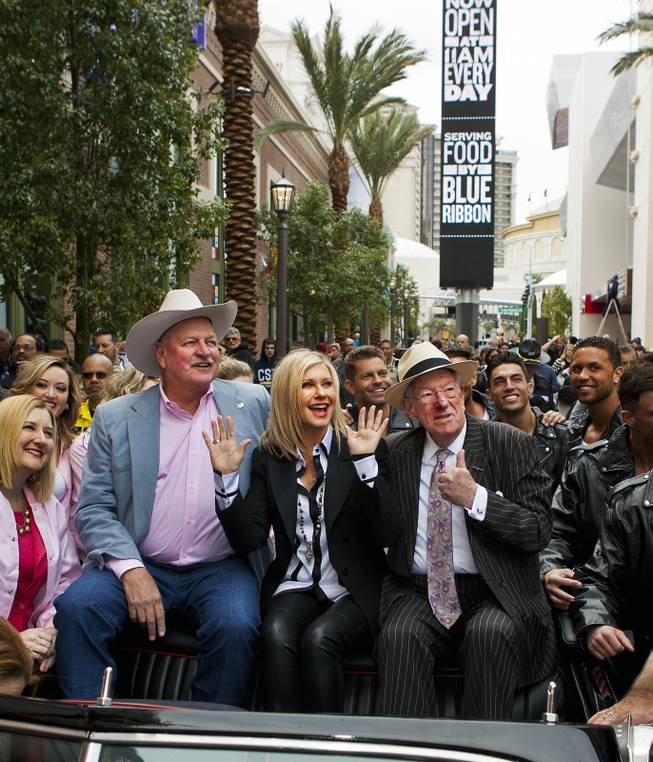 Clark County Commissioner Tom Collins, Olivia Newton-John and Las Vegas Host Committee Chairman Oscar Goodman enjoy the view from a restored T-Bird at the Linq on Wednesday, April 2, 2014.