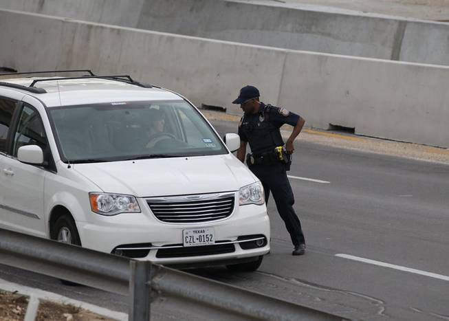 A police officer checks drivers' IDs outside the main gate at Fort Hood, Texas, after a shooting at the Army base Wednesday, April 2, 2014.  One person was killed and at least 14 injured in a shooting Wednesday at Fort Hood.