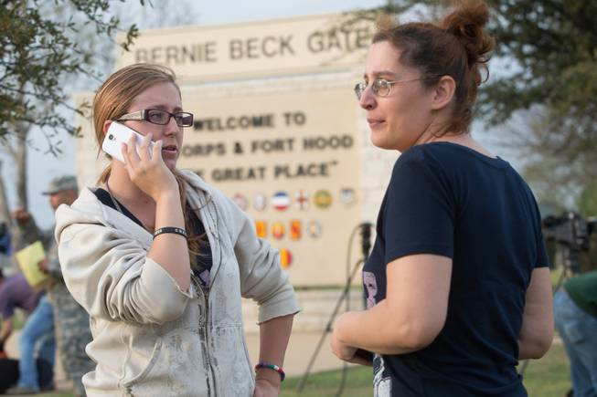 Krystina Cassidy and Dianna Simpson attempt to make contact with their husbands who are stationed inside Fort Hood, while standing outside of the Bernie Beck Gate, on Wednesday, April 2, 2014, in Fort Hood, Texas. One person was killed and 14 injured in a shooting Wednesday at Fort Hood, and officials at the base said the shooter is believed to be dead.