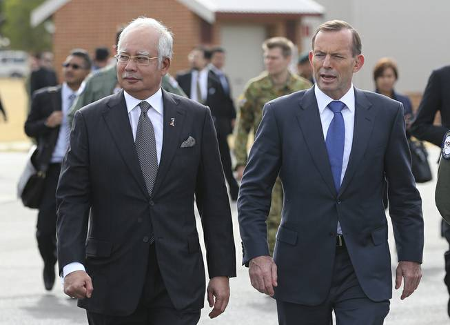 Malaysian Prime Minister Najib Razak, left, walks along the tarmac with Australian Prime Minister Tony Abbott on their way to meet crew members involved in search of wreckage and debris of the missing Malaysia Airlines MH370 in Perth, Australia, Thursday, April 3, 2014.