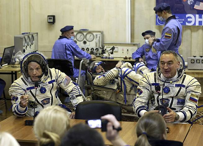 U.S. astronaut Steven Swanson, left, and Russian cosmonaut Alexander Skvortsov, crew members of the mission to the International Space Station, speak with relatives during pre-launch preparations at the Russian-leased Baikonur cosmodrome in Kazakhstan, March 25, 2014. Cosmonaut Oleg Artemyev is at center background.
