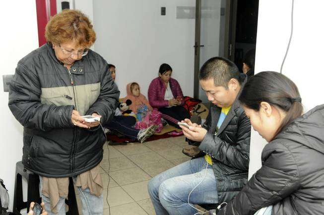 People use their phones on the upper floor of an apartment building located a few blocks from the coast where they gathered to avoid a possible tsunami after an earthquake in Iquique, Chile, Tuesday, April 1, 2014. A powerful magnitude-8.2 earthquake struck off northern Chile on Tuesday night, setting off a small tsunami that forced evacuations along the country's entire Pacific coast.  (AP Photo/Cristian Viveros) NO PUBLICAR EN CHILE