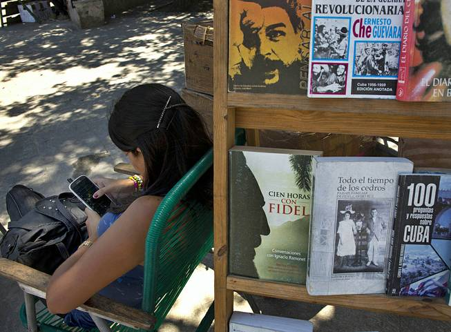 A book street vendor passes the time on her smart phone as she waits for customers in Havana, Cuba, Tuesday, April 1, 2014. The Obama administration secretly financed a social network in Cuba to stir political unrest and undermine the country's communist government, according to an Associated Press investigation.